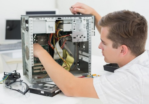 Young technician working on broken computer in his office